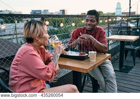 Young intercultural couple having fastfood and drinks while relaxing by table in outdoor cafe