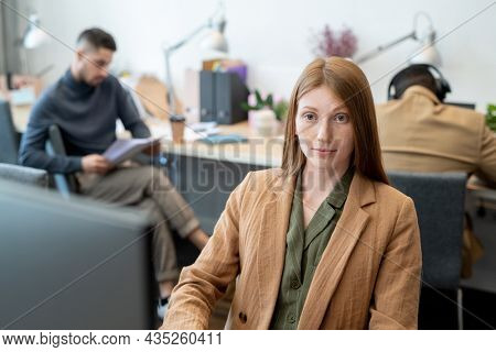 Young elegant businesswoman sitting in front of computer monitor against two male co-workers