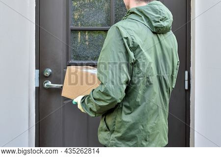 Postman Stands At The Door Of The House And Holds The Parcel In His Hands. Delivery Of The Parcel Co