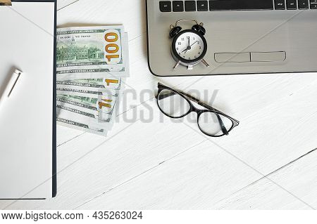 Top View Flat Lay Of Modern Workplace Of Laptop, Clock, Money, Dollars Banknote