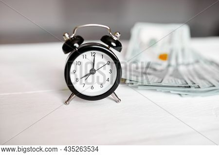 Alarm Clock And Money On White Wooden Background