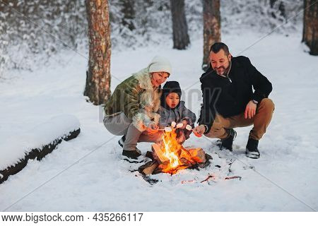 Cheerful Parents And Son Enjoying Hot Drink While Resting Near Campfire In Evening In Winter Forest
