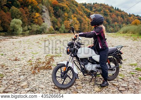 Woman Biker Travel By Motorbike In Fall. Motorcyclist Enjoys Autumn Landscape In Mountains Having Re
