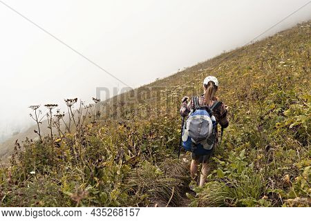 Rear View Of Young Woman In Plaid Shirt With Big Backpack With Trekking Poles Walking Along Mountain