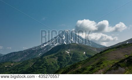 A Beautiful Conical Volcano With Snow-covered Slopes Against A Blue Sky Background. Cumulus Clouds N