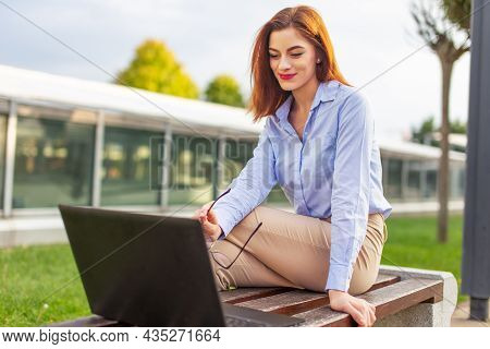 Young Redhead Caucasian Businesswoman At Park Smiling Into Laptop