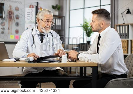 Handsome Man In Business Clothes Visiting Family Doctor For Medical Consultation. Senior Male Doctor