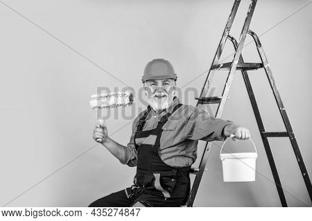 To Make Repairs. Man In Working Clothes Painting Wall In Empty Room. Painter In Overall And Cap With