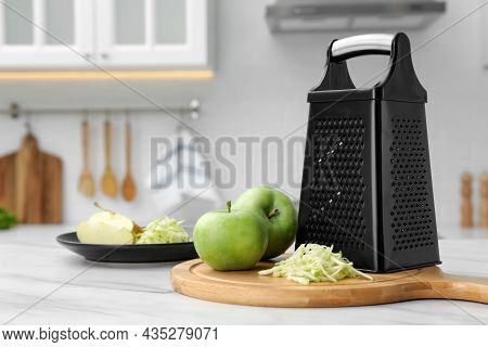 Grater And Fresh Ripe Apples On White Table In Kitchen. Space For Text
