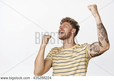 Victory And Celebration. Young Blond Male Model, Fan Celebrating, Shouting Yes And Making Fist Pump