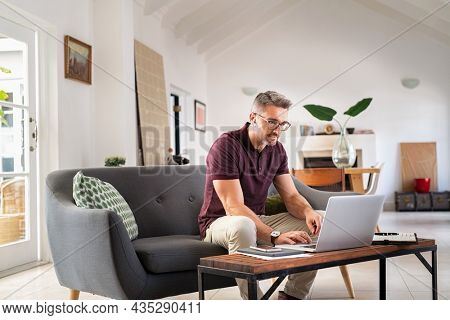 Mature businessman working from home on laptop with copy space. Mid adult entrepreneur focusing on work while working on laptop. Manager wearing eyeglasses while working on laptop for project.