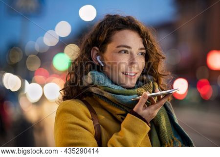 Happy woman recording message using voice on smartphone. Happy woman recording audio on mobile phone in the street at evening. Smiling woman speaking on her smart phone in winter evening.