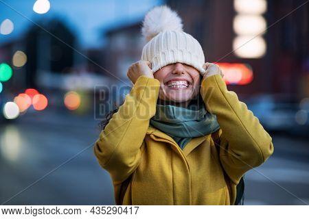 Young playful woman covering eyes with winter cap on city street. Laughing woman on road covering eyes and having fun in a cold winter evening. Happy casual girl having fun during dusk.