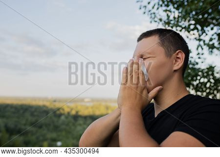 A Man Blinks Into A Handkerchief In The Street. A Man Sneezes In A Handkerchief In The Street.