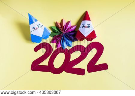 Paper Santa Clauses And A Multicolored Snowflake On A Yellow Background. Origami Figures Of 2022 And