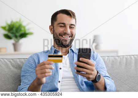 Smiling Satisfied Adult Caucasian Man With Beard Holds Credit Card And Pays Money Online Banking On