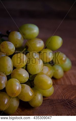 Bunch Of Green Grapes Lies On Wooden Table. Surface Texture Of Raisin Grapes On Brown Background. Ri