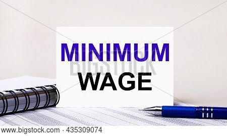 On A Light Gray Background, A Notebook, A Blue Pen And A Sheet Of Paper With The Text Minimum Wage.