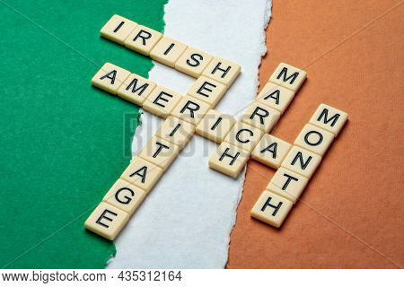 March - National Irish American Heritage Month, crossword on a paper abstract in colors of national flag of Ireland (green, white and orange), reminder of cultural event and celebration