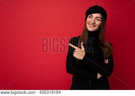 Attractive Emotional Positive Joyful Happpy Female Promoter Pointing To The Side At Copy Space For A
