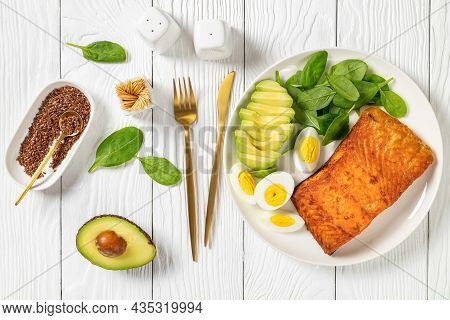 Baked Salmon Fillet With Creamy Ripe Avocado, Baby Spinach And Hard Boiled Eggs On A White Plate On