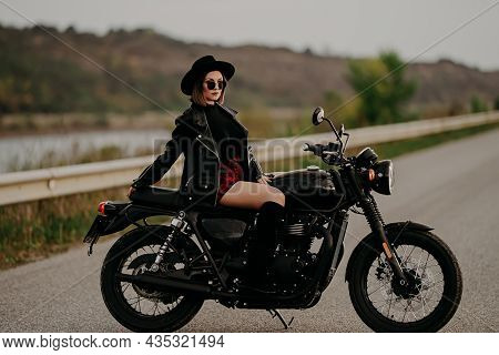 Motorcyclist Woman In Mini Skirt Sitting On Retro-styled Motorcycle. Sexy Female Driver In Jackboots