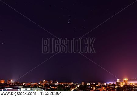 The Constellation Orion Shines Brightly In The Dark Sky Over Illuminated City Skyline At Midnight. C