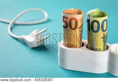 Fifty And One Hundred Euro Banknotes Plugged Into A White Power Strip Over Blue Bacground. Increasin