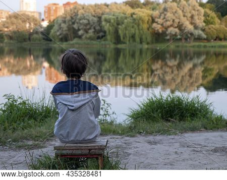 Little Boy Is Sitting Ashore Of Lake And Contemplating. Person Sitting On A Bench Alone And Watching