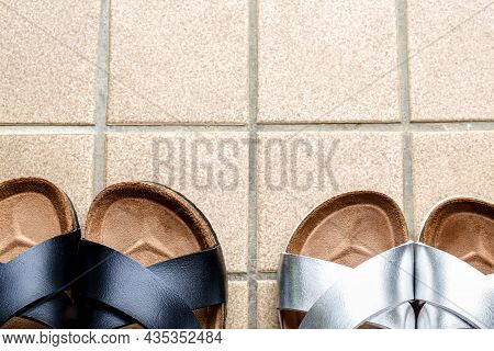 Two Pair Of Slipper On Skin Of Silver With Black On Beige Tiles Background And Copy Space.
