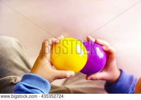 Hands Holding Purple And Yellow Two Balls And Copy Space.