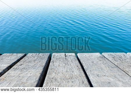Blue Water Calm Waves Surface As Old Wooden Tables Background.calm Water Surface With Small Ripples.
