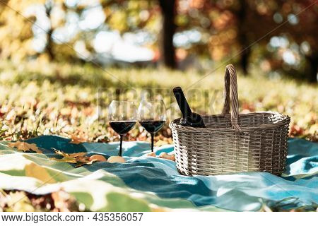Basket,blanket,wine And Glasses On Yellow Autumn Leaves,next To A Tree. A Cozy Autumn Picnic In The