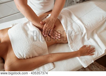 Young Woman Receiving Abdominal Massage In Spa Salon