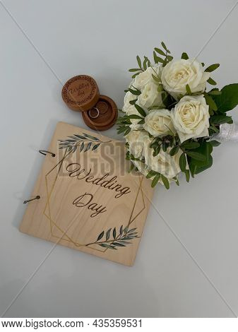 A Wooden Box With A Ring, A Wedding Bouquet And A Plaque With The Inscription Wedding Day On A White