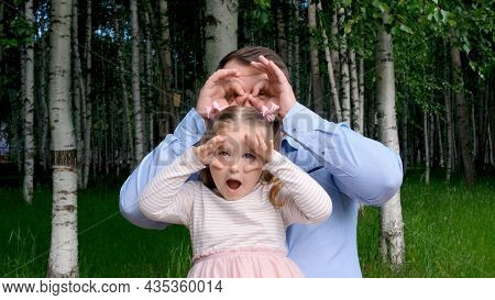 Little Daughter 3 Years Old And Father Are Having Fun On The Street, Making Funny Faces, Making Glas