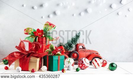 Christmas or New Year gift boxes and Christmas ornaments on wooden table. Festive decorations and presents for winter holidays.