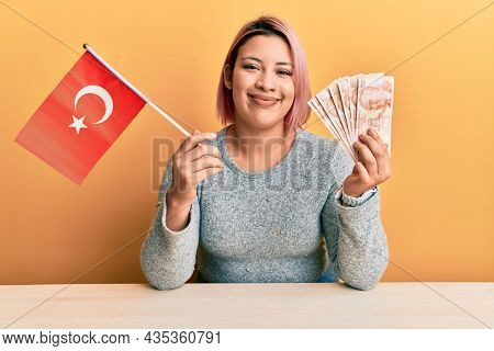 Hispanic woman with pink hair holding turkey flag and liras banknotes smiling with a happy and cool smile on face. showing teeth.