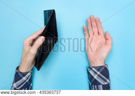 Young Man Holding An Empty Wallet On A Blue Background. Financial Literacy. Bankrupt. Money Is Tight