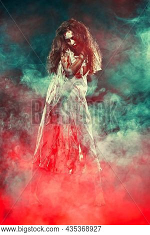 Horror scene of a creepy obsessed woman covered with blood standing in the dark with scary red and green smoke. Bloodthirsty zombie woman. Horror movie, thriller. Halloween.