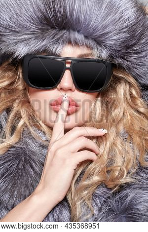 Portrait of an attractive blonde woman in fashionable black glasses and a silver fox fur coat brings her index finger to her sensual lips as a sign of a secret. Fur coat and glasses fashion.