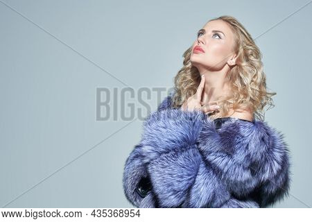 Beautiful woman with curly blonde hair and elegant makeup poses in an expensive silver fox coat with a bare shoulder. Fur coat fashion. Studio portrait on a grey background with copy space.