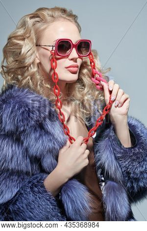 Fur coat and sunglasses fashion. Portrait of a gorgeous blonde woman in an expensive silver fox fur coat and stylish red glasses. Studio portrait. Luxury style.