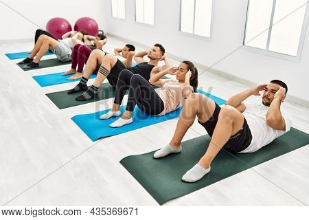 Group of young hispanic people concentrate training abdominal exercise at sport center.