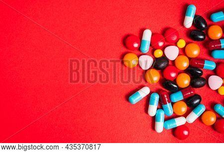 A Lot Of Pill On The Red Background. Medicine Pills, Tablets And Capsules With Copy Space For Text.