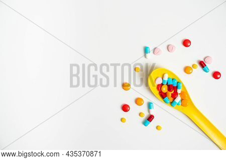 A Lot Of Pills Colorful In Yellow Plastic Spoon On The White Background. Medicine Pills, Tablets And