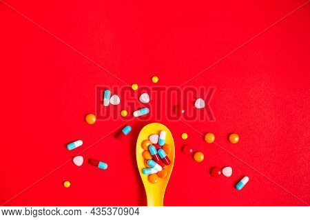 A Lot Of Pills Colorful In Yellow Plastic Spoon On The Red Background. Medicine Pills, Tablets And C