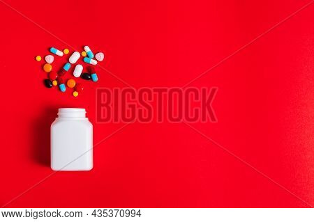 A Lot Of Pills Spilling Out Of A Bottle On The Red Background. Medicine Pills, Tablets And Capsules