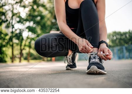 Young girl woman wearing black sportwear sitting at stadium and ties shoelaces preparing for active workout. Fitness training for female outside. Person during exercising
