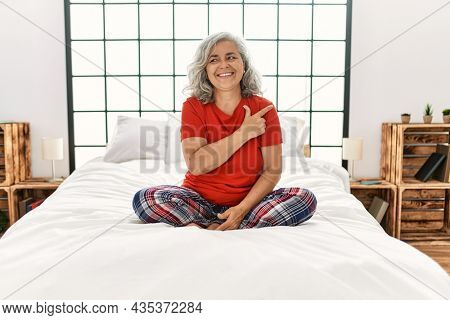 Middle age woman with grey hair sitting on the bed at home cheerful with a smile of face pointing with hand and finger up to the side with happy and natural expression on face